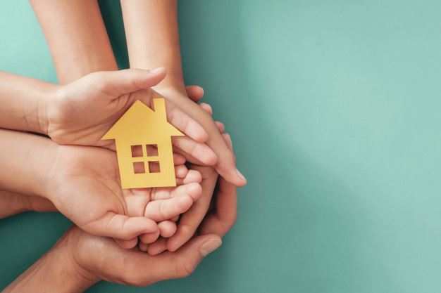 hands-holding-yellow-paper-house-blue-surface-family-home-homeless-shelter-housing-home-protecting-i